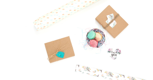 A wrapped gift, wrapping paper and sweets against a white background.