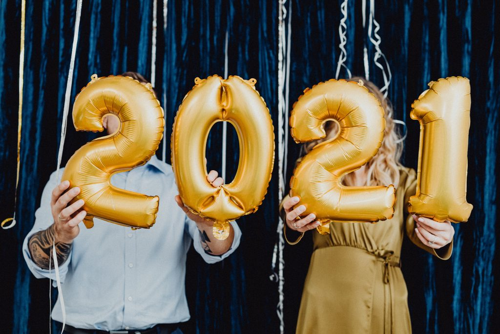 Two people holding up balloons reading 2021.